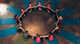 Yogis in orderly circle holding hands